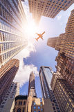 Plane over highrise buildings Stock Photo