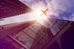 Plane over highrise buildings Royalty Free Stock Photo