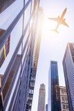 Plane over modern buildings Stock Photo