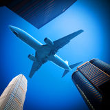 Plane over modern city Stock Photography