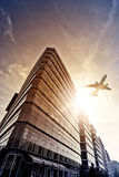 Plane over office complex. Plane flying over modern glass and steel office complex in Berlin, Germany Stock Photo