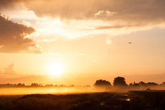 Plane over rural field in fog Royalty Free Stock Photo