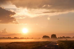 Plane over rural road in fog Royalty Free Stock Photos