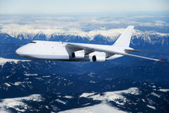 Plane over the sky. Cargo airplane in fly with mountain with snow on background Stock Photo