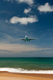 Plane over a tropical beach Stock Photos