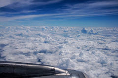 The plane over the white clouds Stock Photo