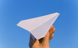 Plane paper. In a hand against the blue sky Royalty Free Stock Image