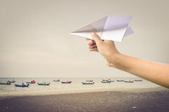Plane paper in children hand over sea and boats royalty free stock photo