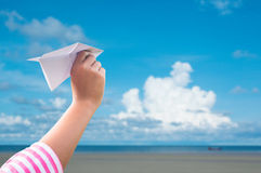 Plane paper in children hand over seaand blue sky Royalty Free Stock Photos