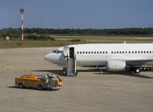 Plane parked at the airport. With support car Royalty Free Stock Images