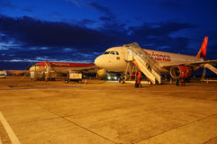 Plane parked into airport for maintenance and refuel. Stock Photos