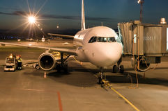 Plane parked at the airport at night Stock Images
