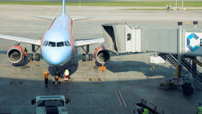 A plane is parked for the tunnel to be attached stock video footage
