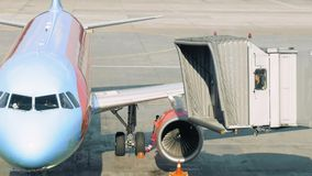 A plane is parked for the tunnel to be attached stock footage