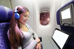 Plane passenger in airplane using tablet computer Stock Photography