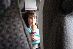 Plane passenger child watching inflight movie. Plane passenger child girl age 6-7 . Child in in airplane cabin watching inflight movie / listening to music on royalty free stock photography