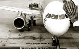 The plane with the passenger gangway at the international airport. Stock Photos
