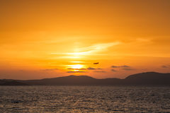 Plane passing through setting sun at Calvi in Corsica Stock Images
