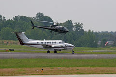 Plane and Police Chopper. Small plane landing Royalty Free Stock Photos