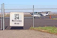 Plane ready for take off. A small plane sits behind a chain link fence and secured area at the Logan Airport in Billings, Montana stock image