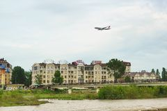 The plane of Red Wings airline comes to land above the hotel in the resort of Adler. Cloudy day in early summer. Russia, Sochi, Krasnodar region-June 07.2017 Stock Photos