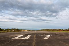 Plane runway, airstrip in the airport terminal with marking on blue sky with clouds to use as background. Travel Royalty Free Stock Photos
