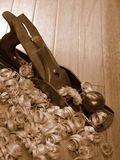 Plane shavings. Old time woodworking plane with curly cedar wood shavings Royalty Free Stock Photography