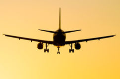 Plane silhouette. On an orange evening sky on sunset Stock Images