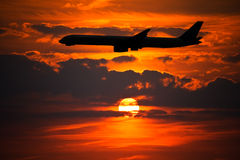 Plane Silhouette at Sunset. Plane Silhouette against Setting Sun Stock Photos