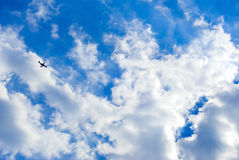 Plane in the sky. With a lot of clouds Stock Photography