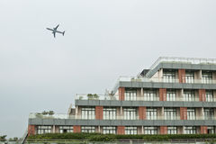 A plane in the sky. A plane flies through the sky above a building Stock Image
