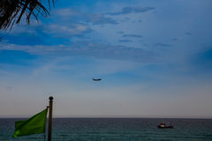 plane in sky above sea fishing boat green banner on foreground Stock Photography