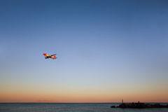 Plane in the sky. Plane is flying in the sky above beach Royalty Free Stock Image