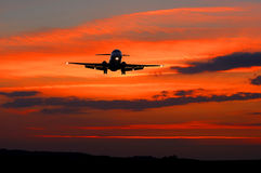 Plane on the sky orange. Big aircraft preparing to land Royalty Free Stock Photo