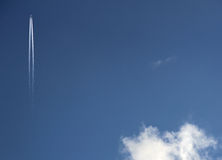 Plane in Sky. Solitary airliner in deep blue sky with single cloud Stock Photography