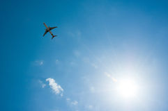 Plane on the sky. Plane taking off on the background of sky and sun Stock Photos
