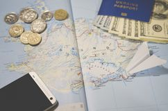 The plane, smartphone, biometric passport, dollars, coins and credit cards lie on a map stock photography