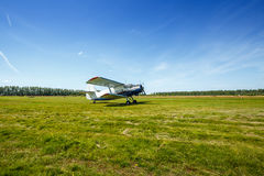 The plane stands on the grass field. The plane takes off from field Royalty Free Stock Photo
