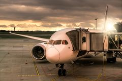 The plane stands with a tunnel at the airport at sunset.  Stock Photo