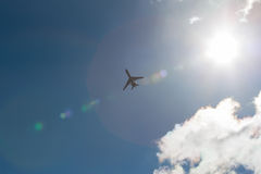 Plane and sun. Pictured on the plane in flight against the blue sky and bright sun Stock Photos