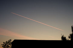 Plane at sunset. Dream house clouds in the sky, followed by an aircraft stock images
