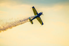 Stunt airplane flying in the twilight sun Royalty Free Stock Photo