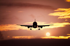 Plane in the sunset sky Royalty Free Stock Photography