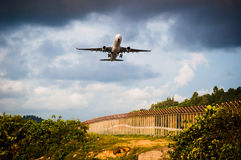 The plane is take off to sky from ariport and over plant, tree a. The plane is take off to sky from airport and over plant, tree and fence among warm light Stock Images