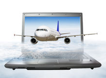 The plane takes off from the laptop screen, soaring in the sky Royalty Free Stock Photos