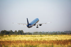 Plane taking off in the airport. Blue-grey cargo airplane taking off Stock Photos