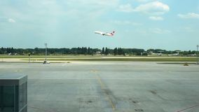 Plane taking off, flying over runway at airport, view from terminal across road. Stock footage stock video