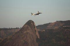 Plane taking off near mountain stock image