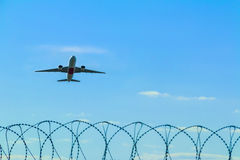 Plane taking off over the barbed wire Stock Photography