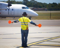 Plane taxiing. A plane arriving with ground staff directing it to the terminal Stock Photo